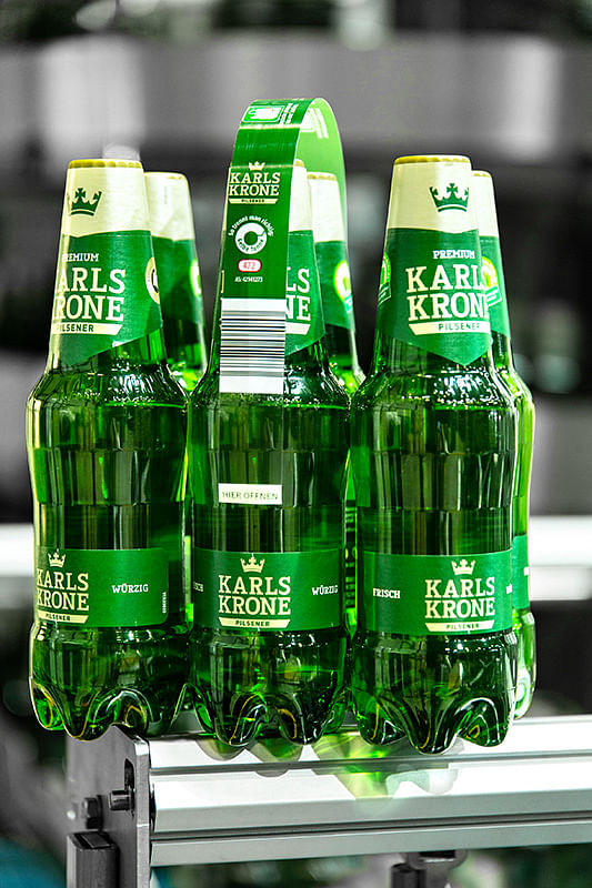 The material-saving Nature MultiPack system from KHS forms cans or PET bottles into stable packs with the help of small dots of adhesive. Martens and KHS have produced film-free six-packs of PET bottles for the retail trade.