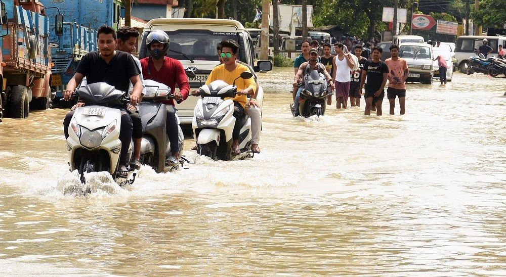 Two-wheeler riders and People wade through a flooded road following heavy monsoon rain at Panikhaiti in Kamrup district of Assam