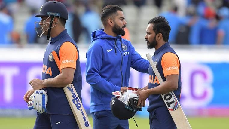 India's captain Virat Kohli (C) greets his players Mahendra Singh Dhoni (L) and Kedar Jadhav (R)