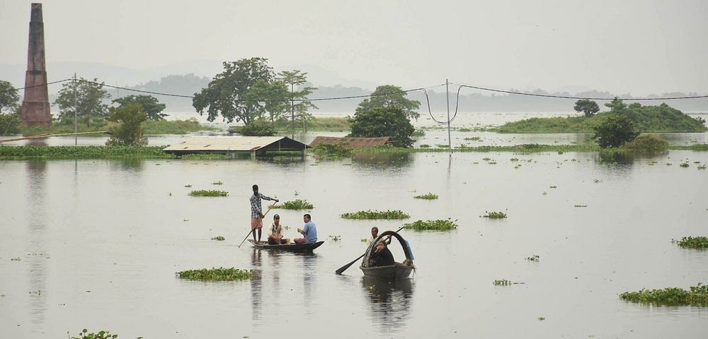 People move to a safer place from a flood-affected area on a boat in the Kamrup District of Assam