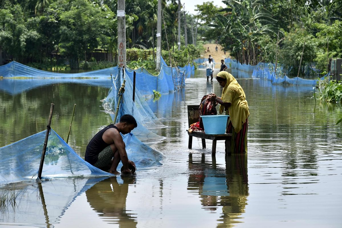 An Indian woman washes clothes next to man cleaning a pot along a flooded road following heavy monsoon rains at Kaljhar village in Barpeta district of Assam