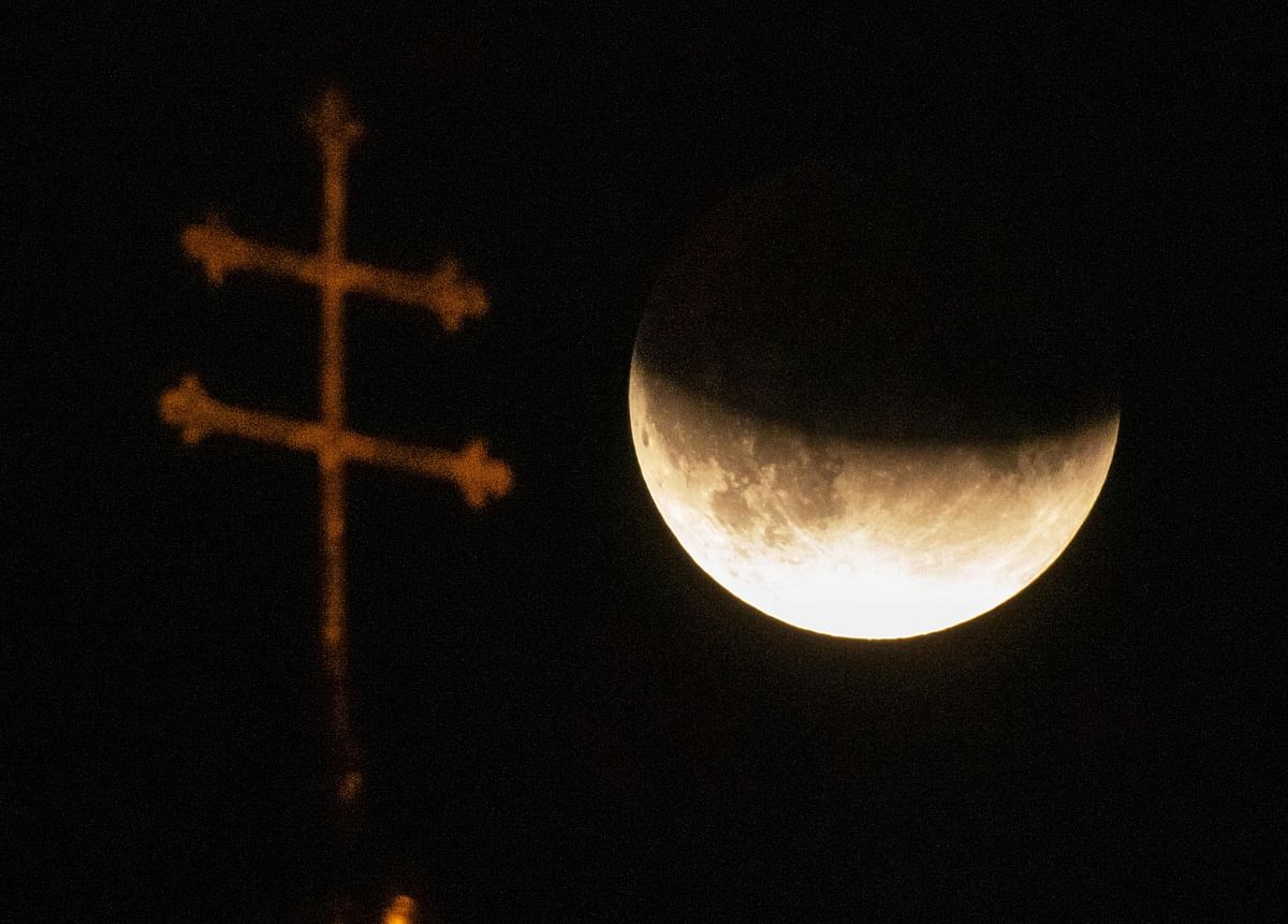 The cross of a church is pictured in front of the moon during a partial lunar eclipse in Munich, Germany, on July 16, 2019.