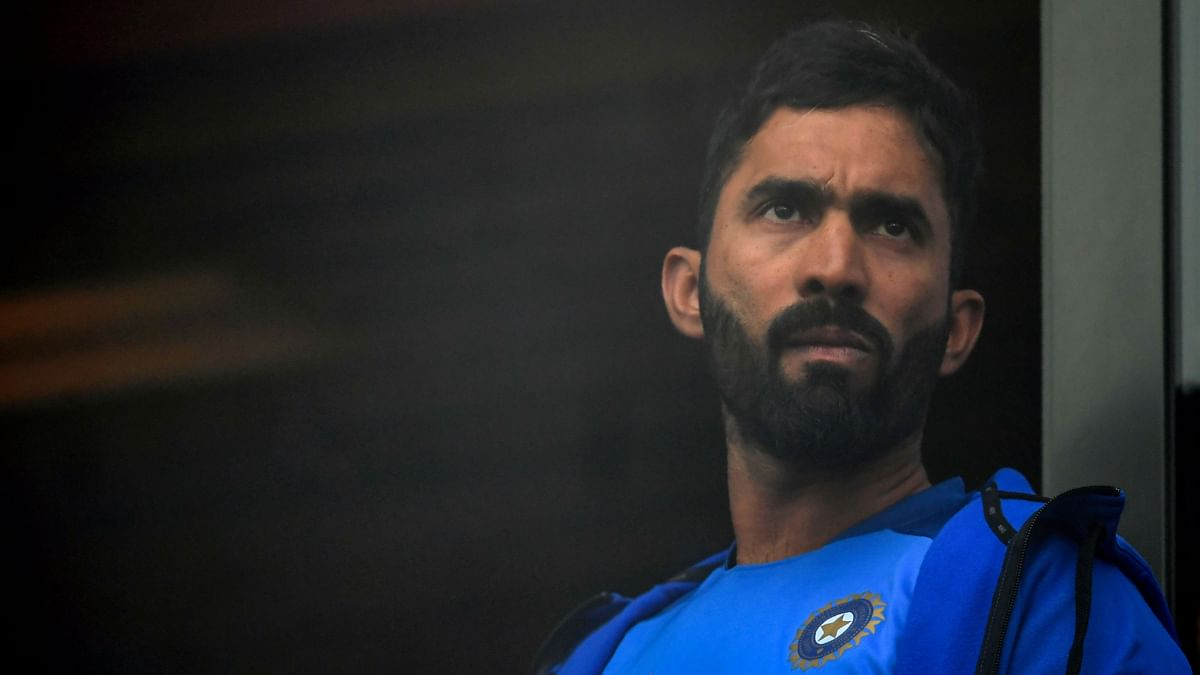 India's Dinesh Karthik looks on from the team dressing room as rain stopped play during the 2019 Cricket World Cup first semi-final between India and New Zealand at Old Trafford in Manchester, northwest England, on July 9, 2019