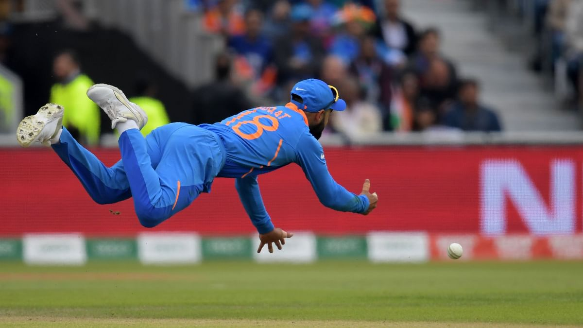 India's captain Virat Kohli dives in the air as he throws the ball during the 2019 Cricket World Cup first semi-final between India and New Zealand at Old Trafford in Manchester, northwest England, on July 9, 2019