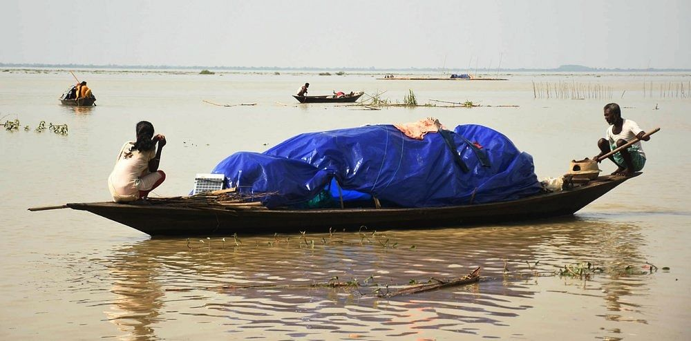 People move to a safer place on a boat from a flood-affected area at Panikhaiti in Kamrup district of Assam