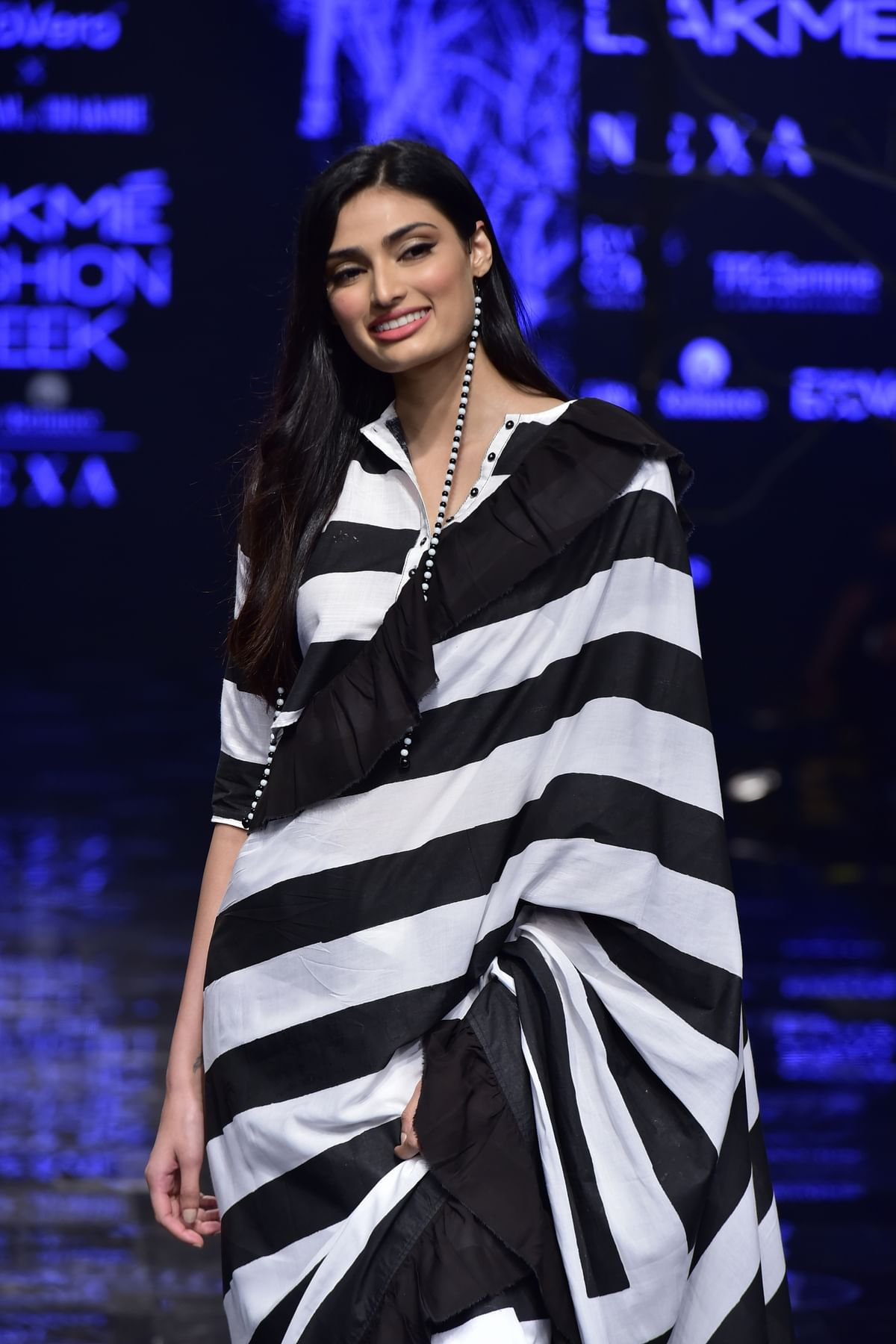 Athiya wore a monochromatic frilled saree in viscose fabric and a matching shirt blouse.