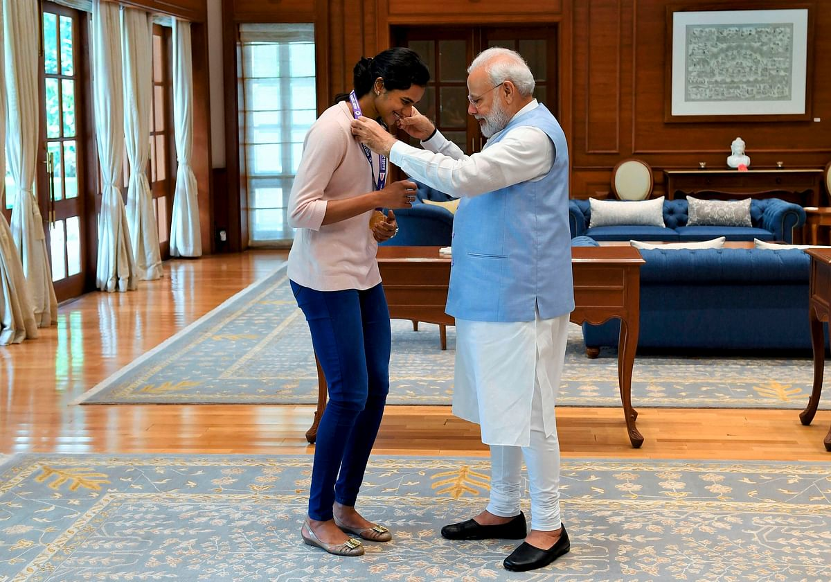 Prime Minister Narendra Modi congratulates World Champion PV Sindhu for her win in the badminton World Championships during a meeting, in New Delhi. Sindhu became the first Indian to win the badminton World Championships by beating familiar rival Nozomi Okuhara of Japan in a lop-sided final in Basel