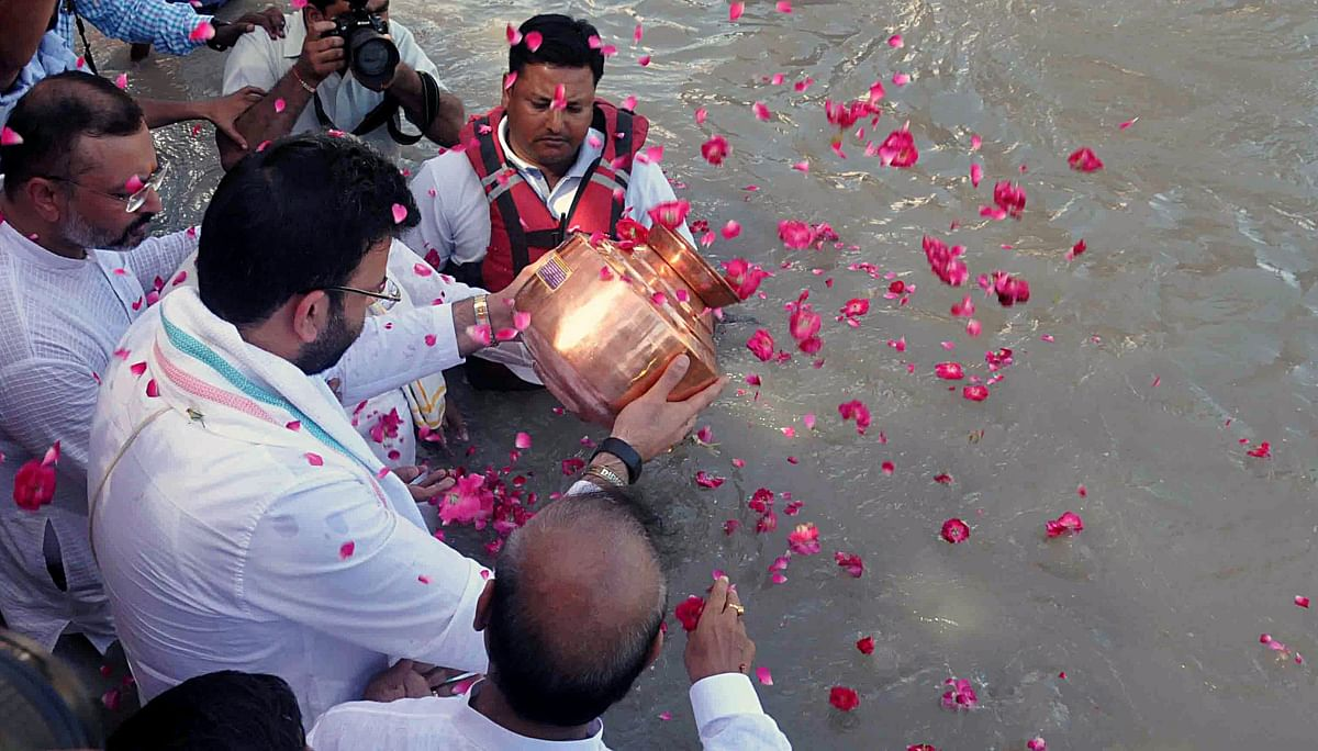 Former Union Minister Jaitley's son, Rohan, immersing his father's ashes in the Ganges.