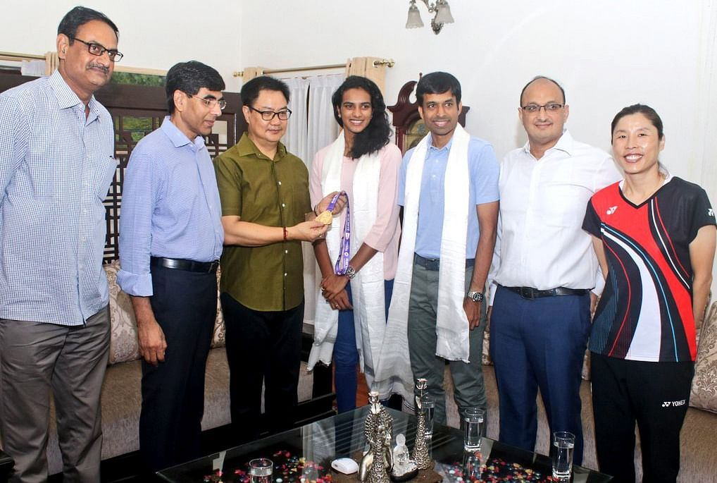 Union Sports Minister Kiren Rijiju meets Badminton Player PV Sindhu after winning a gold medal at the BWF World Championships, at his residence in New Delhi, Chief national badminton coach Pullela Gopichand also present