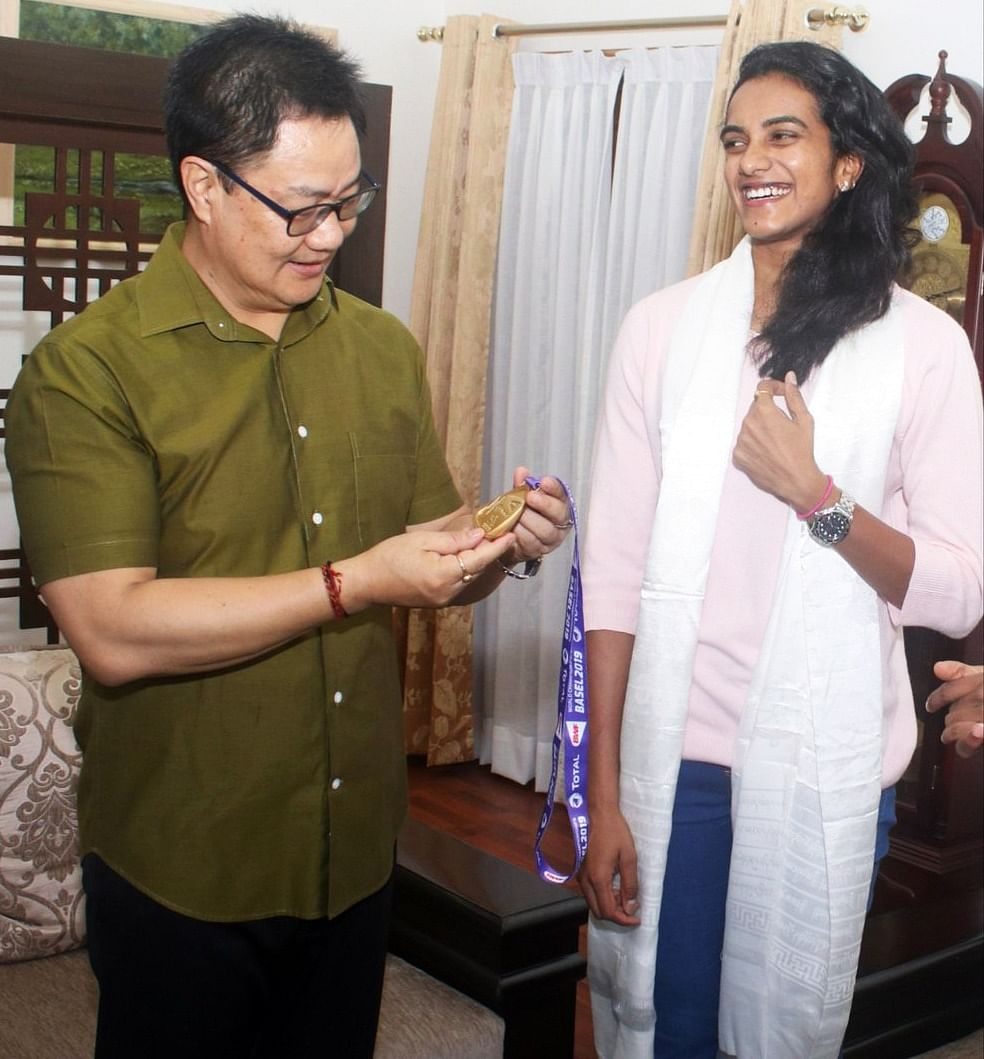 Union Sports Minister Kiren Rijiju meets Badminton Player PV Sindhu after winning a gold medal at the BWF World Championships, at his residence in New Delhi