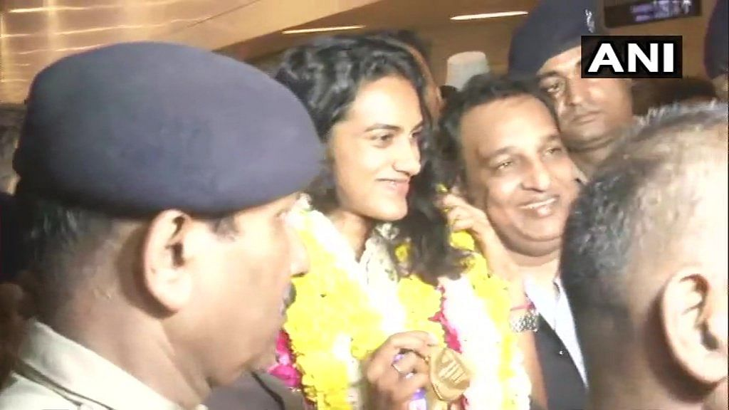 """Delhi: PV Sindhu welcomed at IGI Airport on her return from Switzerland after winning the BWF World Championships, the first-ever Indian shuttler to achieve the feat; says, """"a great moment for me. I am really very proud to be an Indian"""""""