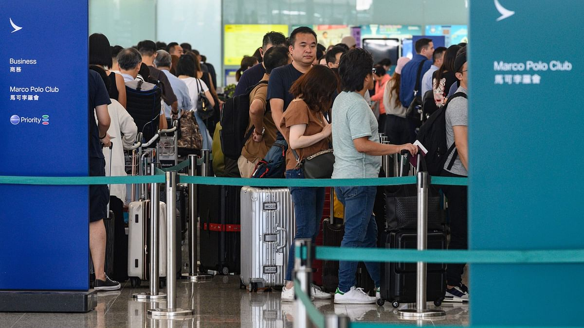 Passengers line up at airline counters at Hong Kong international airport on August 5, 2019