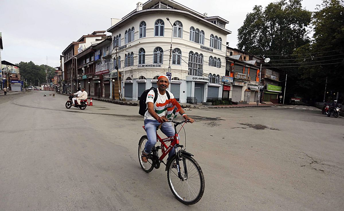 A man rides a bicycle with National flags during the 73rd Independence Day celebration in Srinagar