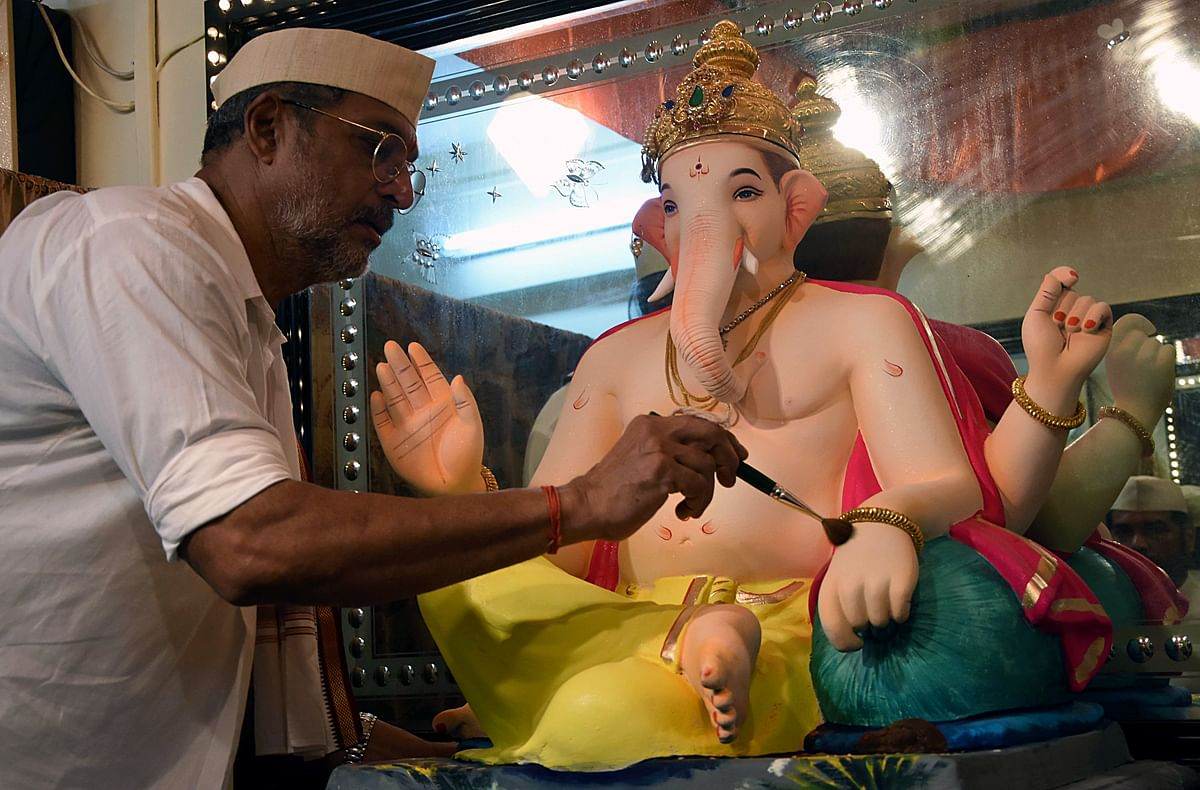 Bollywood actor and social activist Nana Patekar gives a final touch to an idol of Lord Ganesha on the occasion of Ganesha Chaturthi at his residence in Mumbai