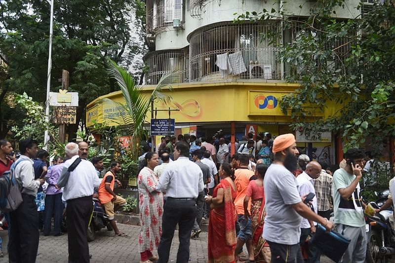 Mumbai: Customers stand outside the Punjab and Maharashtra Cooperative Bank at GTB Nagar in Mumbai, Tuesday, Sept. 24, 2019. The Reserve Bank of India has placed Mumbai-based PMC Bank under directions for six months from the close of business of the bank on September 23, 2019. (PTI Photo/Shashank Parade)  (PTI9_24_2019_000050B)