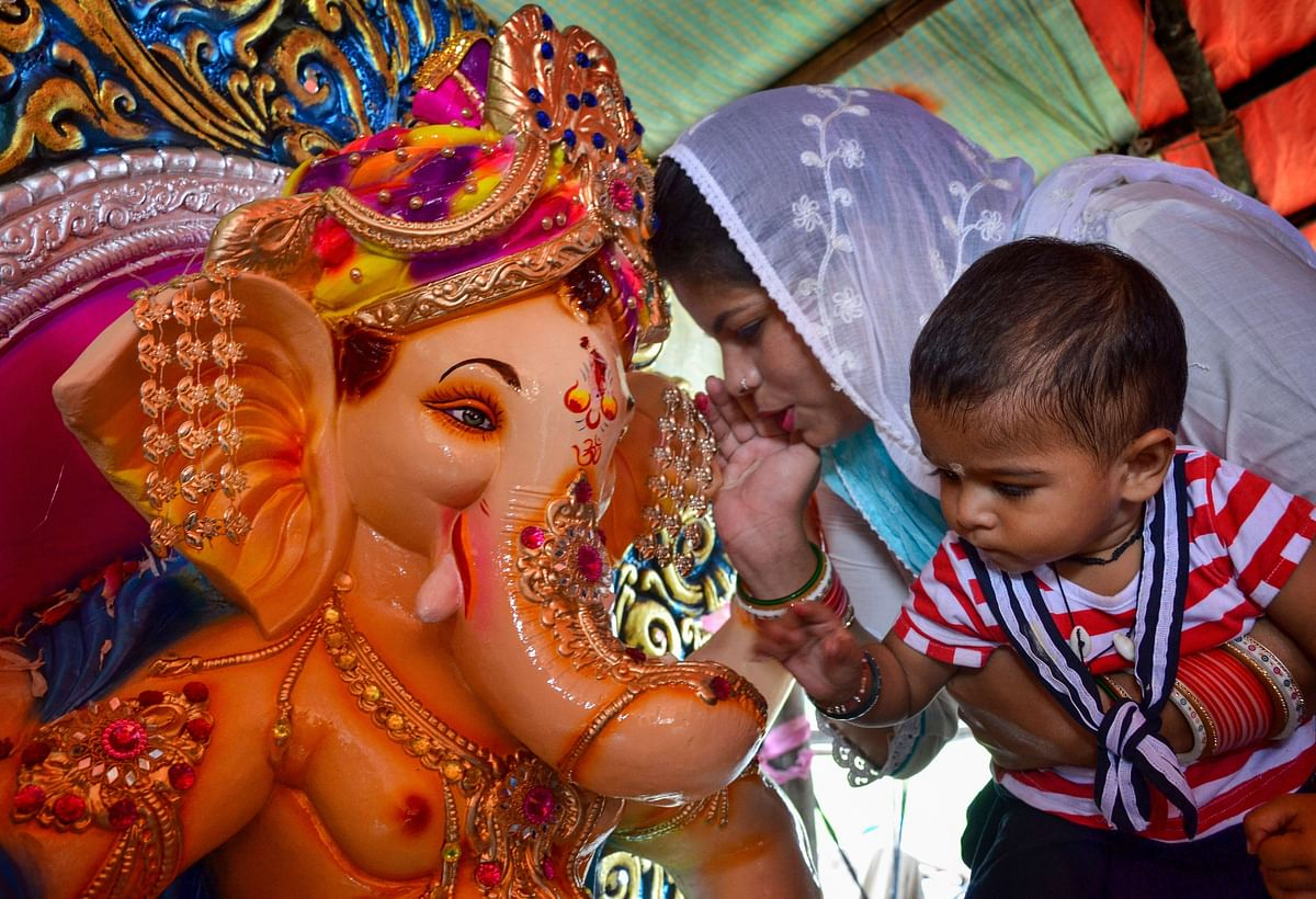 A devotee whispers a wish in the ear of an idol of Hindu God Ganesha as part of a ritual on the occasion of Ganesha Chaturthi, in Amritsar