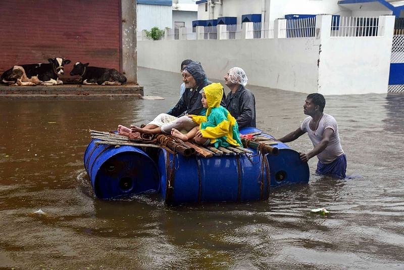 Patna: Peoples sit on a makeshift boat to cross the flood-affected area of Sakha Maidan following heavy monsoon rainfall, in Patna, Sunday, Sept. 29, 2019. (PTI Photo) (PTI9_29_2019_000143B)