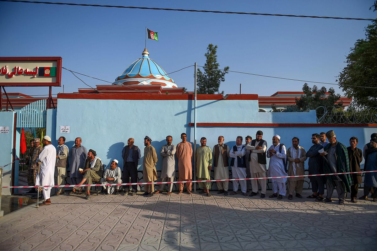 Men queue to cast their vote at a polling station in Mazar-i-Sharif on September 28, 2019. - Insurgents worked to disrupt Afghanistan's presidential election on September 28, with a series of blasts reported across the country as voters headed to the polls and troops flooded the streets of the capital.