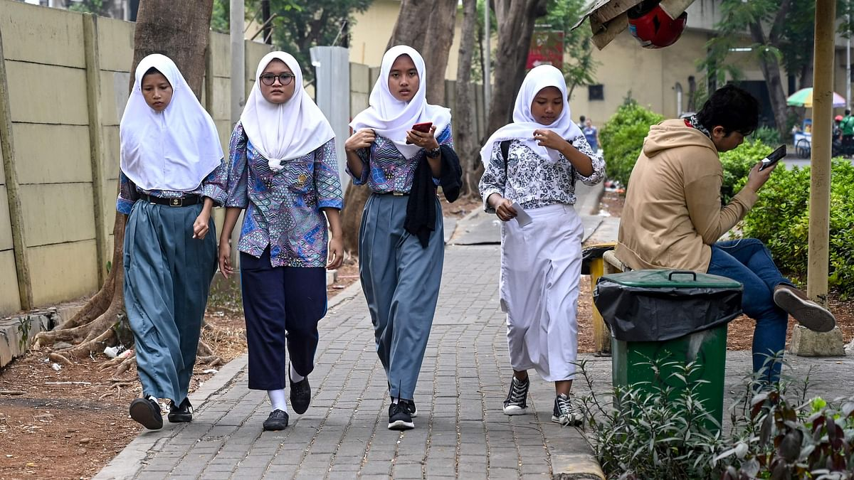 A group of young Muslims wearing hijabs make their way along a street in Jakarta on September 19, 2019. - Indonesia is set to vote on a plan to outlaw gay and pre-marital sex while beefing up its blasphemy laws in a shakeup fuelled by religious conservatism and slammed by rights groups Thursday