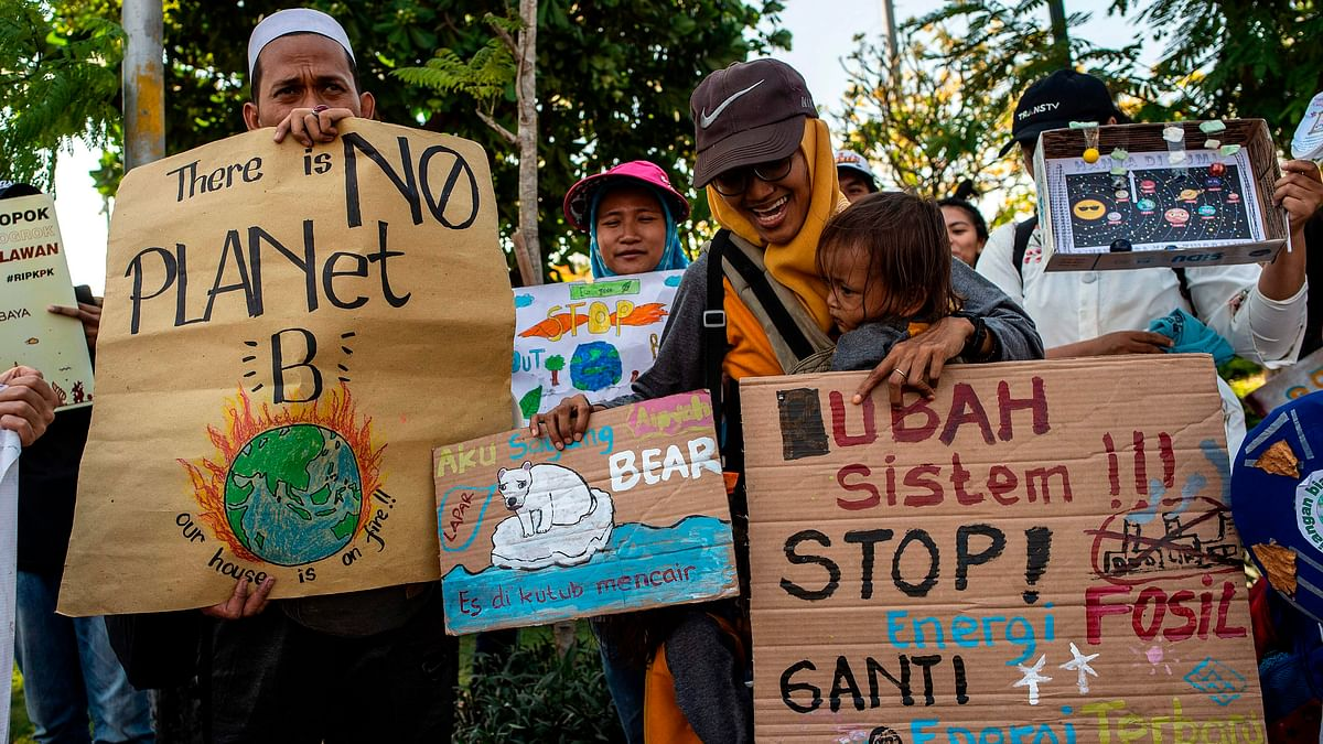 A group of Indonesians hold placards as they take part in a global climate change campaign in Surabaya on September 20, 2019