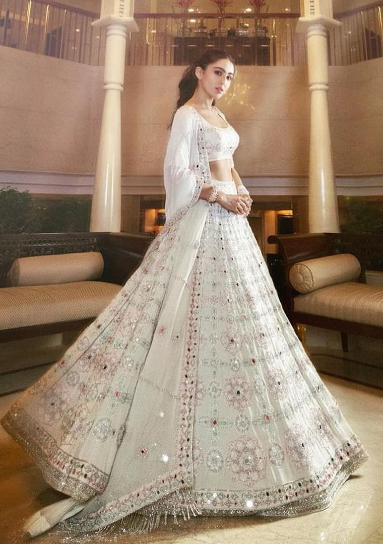 Sara Ali Khan's over the top lehenga choli is sheer elegance. The colour which is a symbol of purity can be enhanced with bold makeup and jewellery.