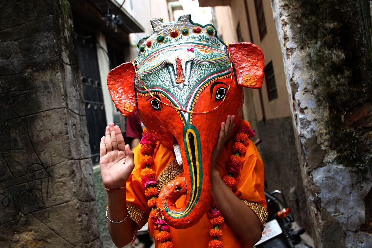 A boy dressed as the elephant-headed Hindu deity Ganesha gestures during Ganesh Chaturthi festival celebration in Pushkar