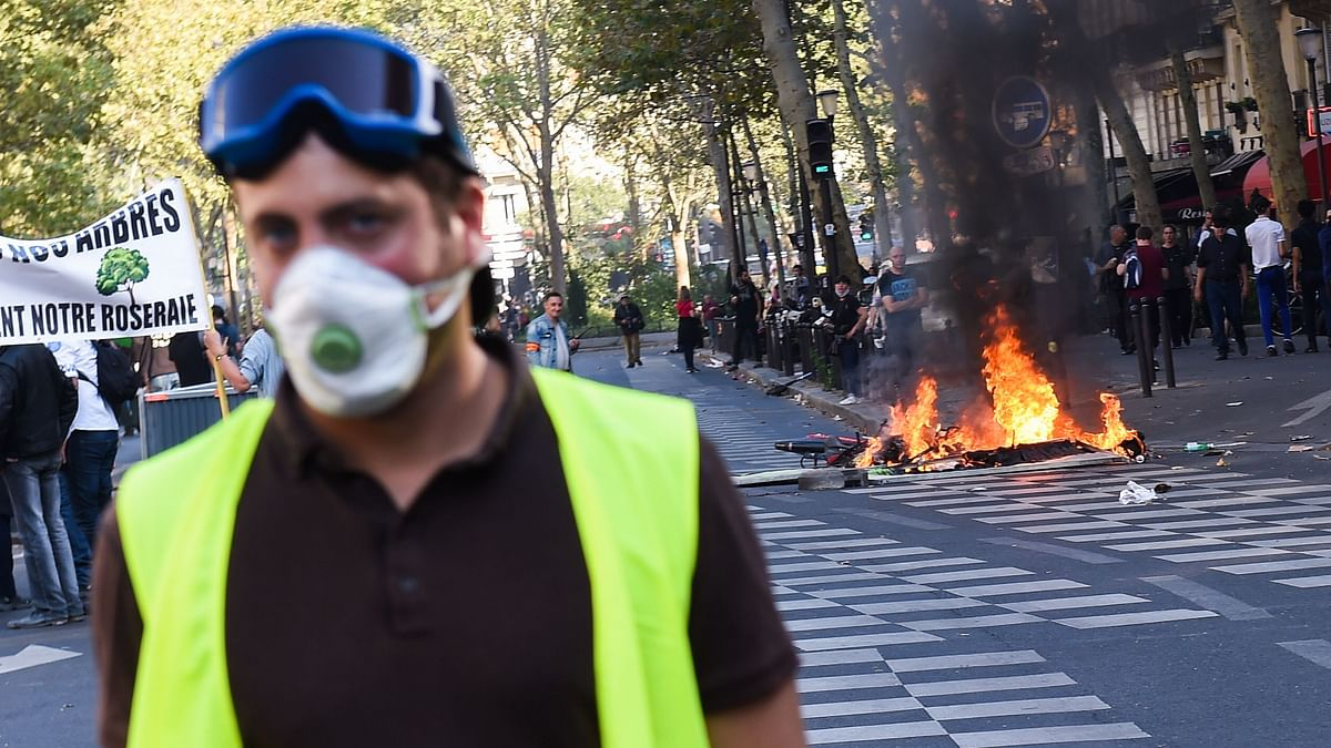 A yellow vest stands in front of burning eletric scooters during clashes with riot police as part of a climate change protest in Paris, on September 21, 2019