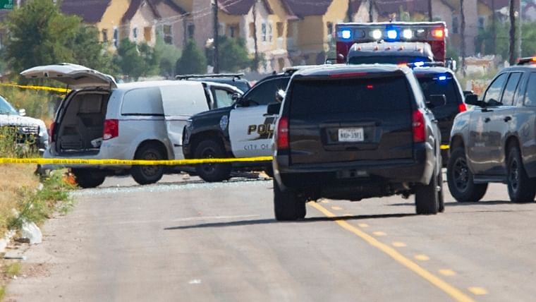 Odessa and Midland police and sheriff's deputies surround a white van in Odessa, Texas, after reports of gunfire.