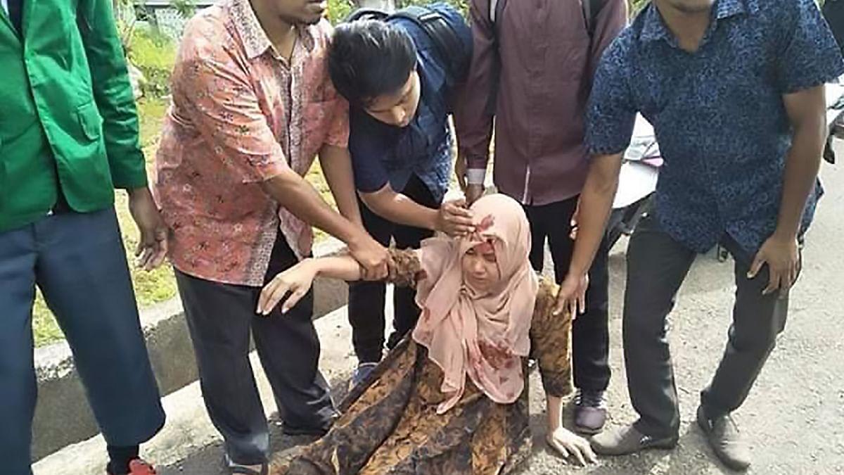 People help an injured woman in Ambon, Indonesia.