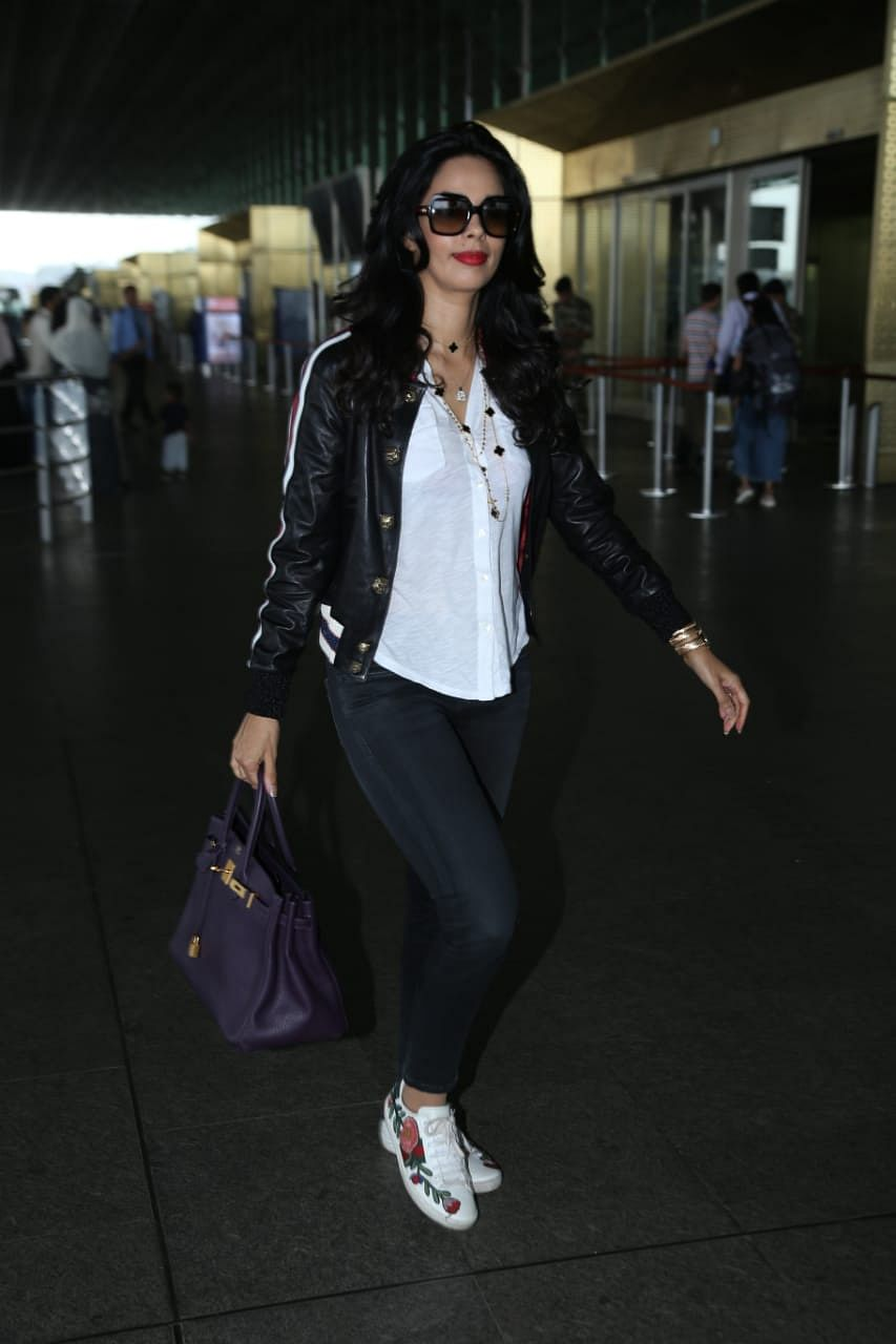 Malika Sherawat was also snapped at the airport in a white shirt with black leather jacket and black jeans.
