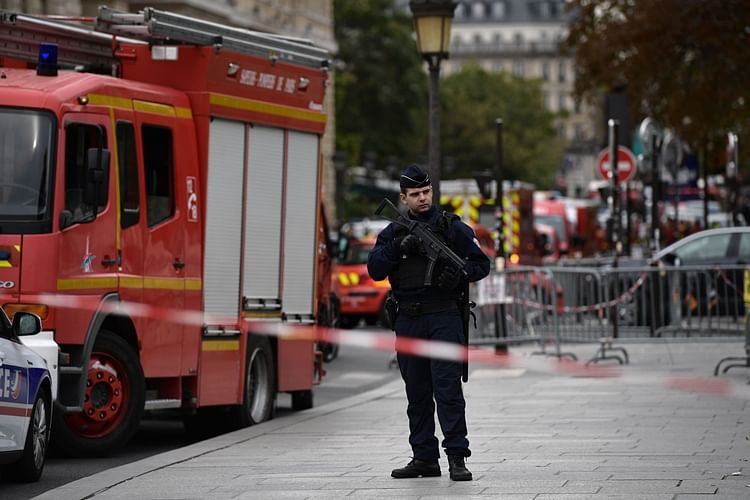 Police stand next to firefighter vehicles near Paris prefecture de police (police headquarters) after four officers were killed in a knife attack.