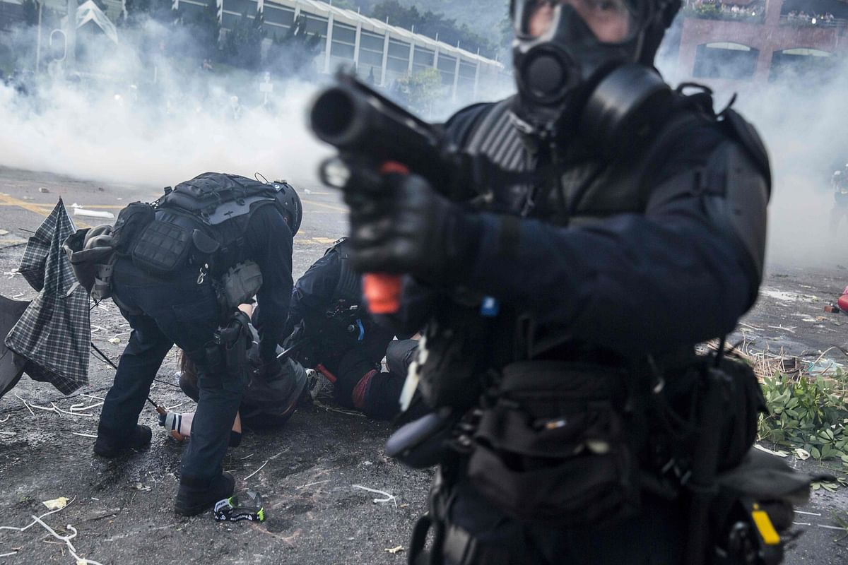 A riot police officer points his projectile launcher as his colleagues detain demonstrators in the Sha Tin district of Hong Kong on October 1, 2019