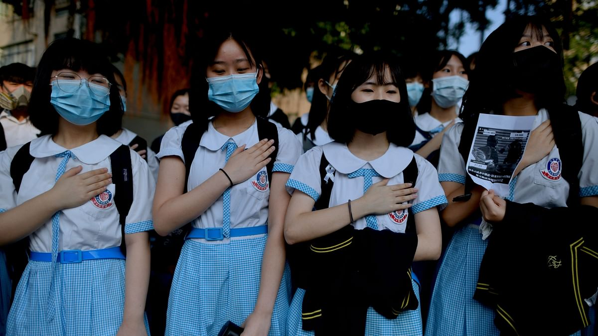 Schoolmates of form five student Tsang Chi-kin, 18, who was shot in the chest by police during violent pro-democracy protests that coincided with China's October 1 National Day, place their hands on their chests during a protest at a school in Hong Kong on October 2, 2019