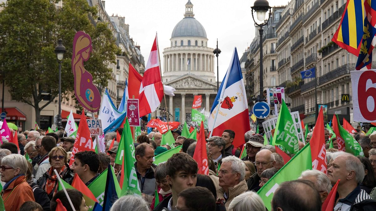Protesters wave flags and hold signs as they take part in a demonstration against a government plan to let single women and lesbians become pregnant with fertility treatments, near the Pantheon in Paris.
