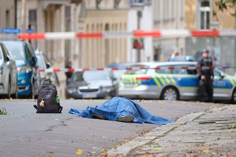 "A body laying in the street is covered as police block the area around the site of a shooting in Halle an der Saale, eastern Germany, on October 9, 2019. - At least two people were killed in a shooting on a street in the German city of Halle, police said, adding that the perpetrators were on the run. ""Early indications show that two people were killed in Halle. Several shots were fired. The suspected perpetrators fled in a car,"" said police on Twitter, urging residents in the area to stay indoors. (Photo by Sebastian Willnow / dpa / AFP) / Germany OUT"