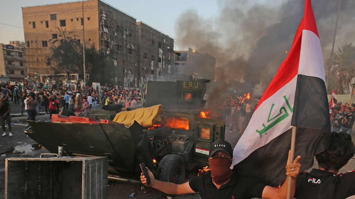 An Iraqi protester holds the national flag next to a burning riot police vehicle during clashes amidst demonstrations against state corruption, failing public services, and unemployment in the Iraqi capital Baghdad's central Tayeran Square