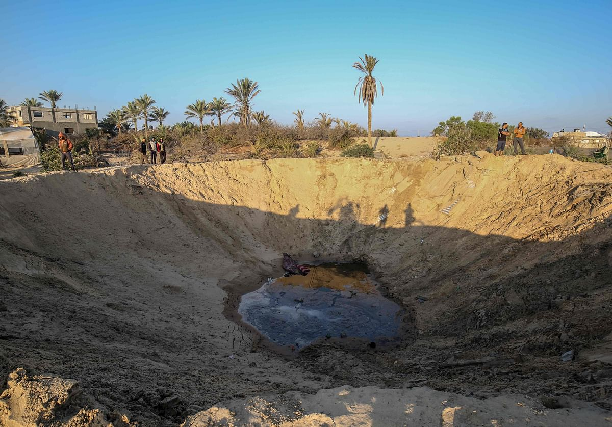 Palestinian men walk around a crater caused by an Israeli airstrike launched in response to rocket fire, in Khan Yunis in the southern Gaza Strip on November 2, 2019.