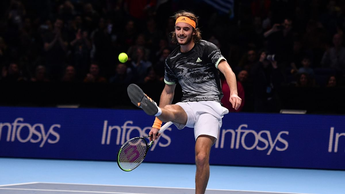 Greece's Stefanos Tsitsipas kicks the ball as he celebrates victory against Switzerland's Roger Federer during the men's singles semi-final match on day seven of the ATP World Tour Finals tennis tournament at the O2 Arena in London on November 16, 2019.