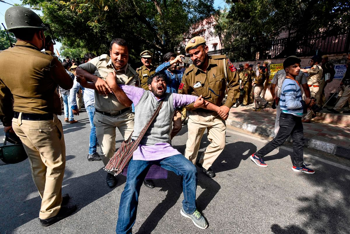 Security personnel hold a Jawaharlal Nehru University (JNU) student during a students protest against hostel fee hike, as security measures have been reinforced from JNU campus along the road to the march protest, in New Delhi on November 18, 2019.