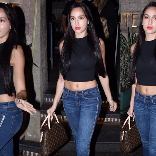 Nora Fatehi flaunts her belly piercing in a black crop top and denim for a casual outing