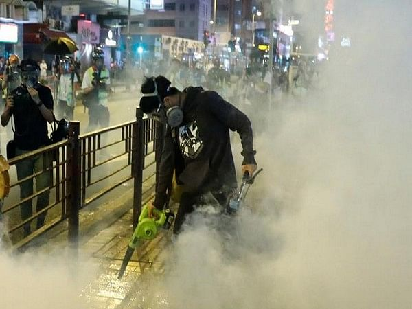A protester uses a leaf blower to disperse tear gas