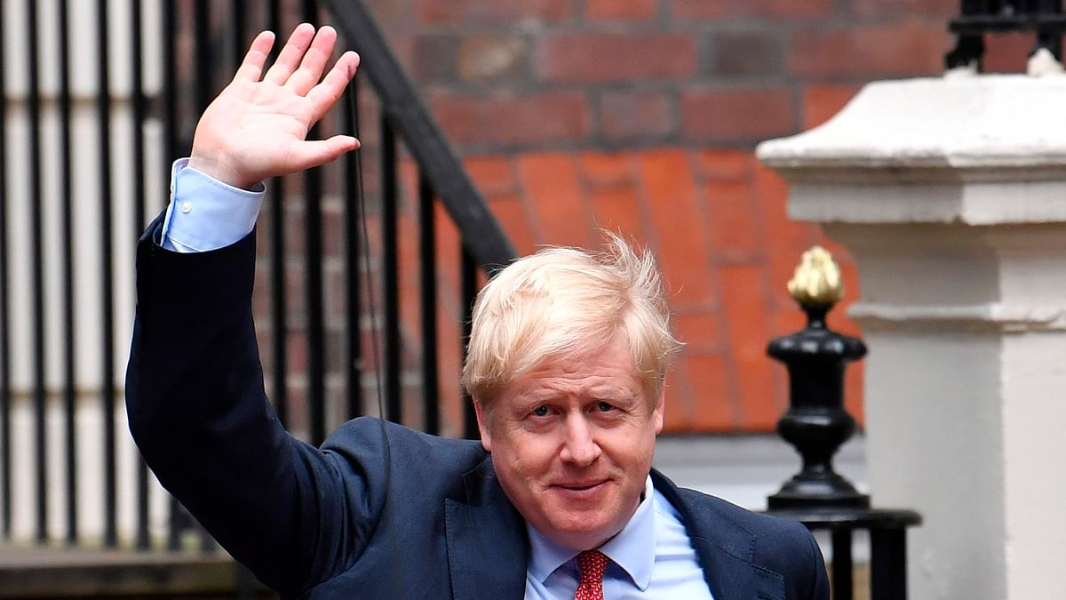 Britain's Prime Minister Boris Johnson (C) waves as he leaves the Conservative Party headquarters in London. Britain goes to the polls on December 12 to vote in a pre-Christmas general election.