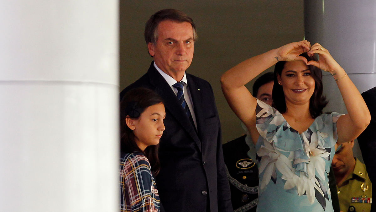 President Jair Bolsonaro (C) First Lady Michelle Bolsonaro and their daughter Laura attend a Christmas event, at the Federal District public school in Brasilia.