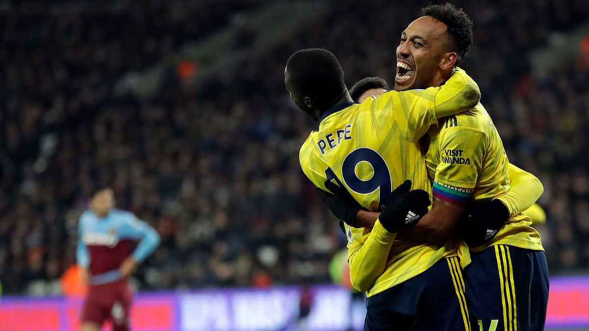 Arsenal's Pierre-Emerick Aubameyang, right, celebrates with teammates after scoring his side's third goal duels for the ball with during the English Premier League soccer match between West Ham Utd and Arsenal at the London Stadium in London.