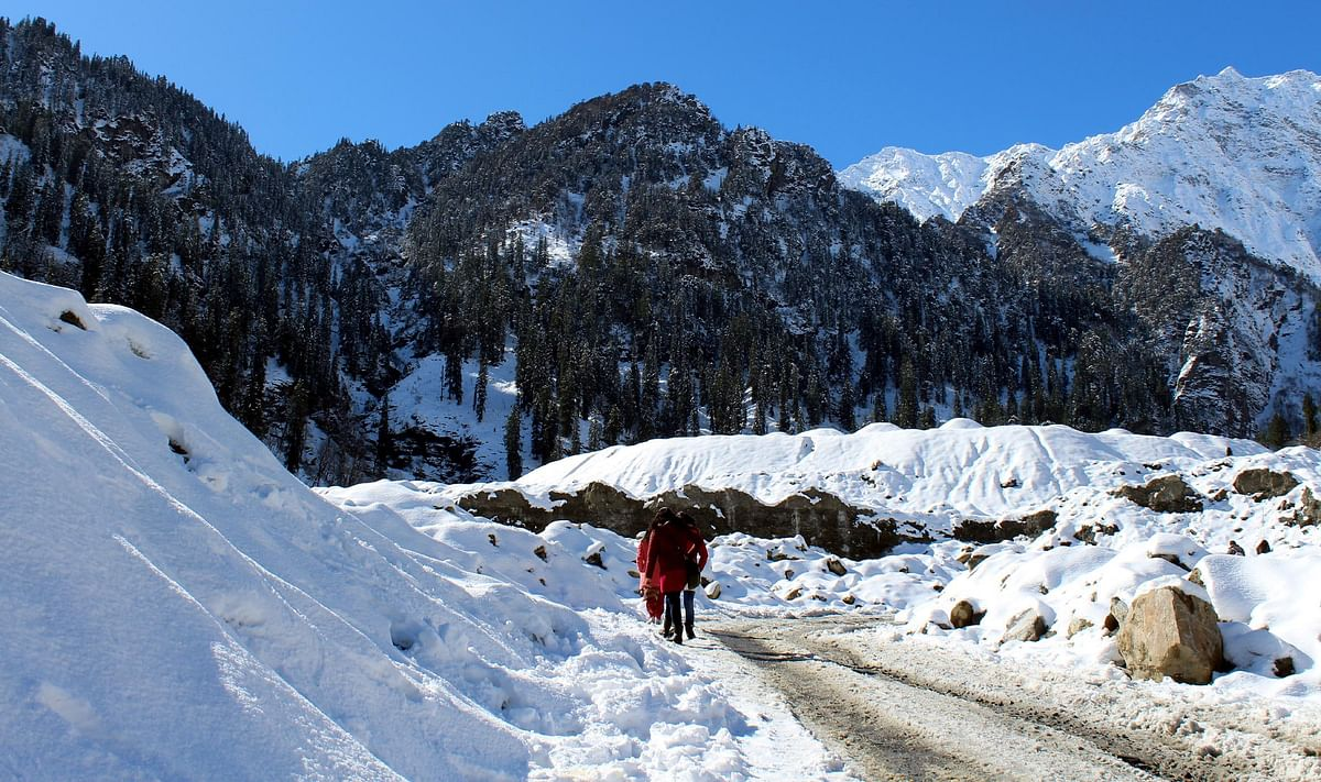 Tourists walking on a snow-covered road at Solang Nala in Manali.