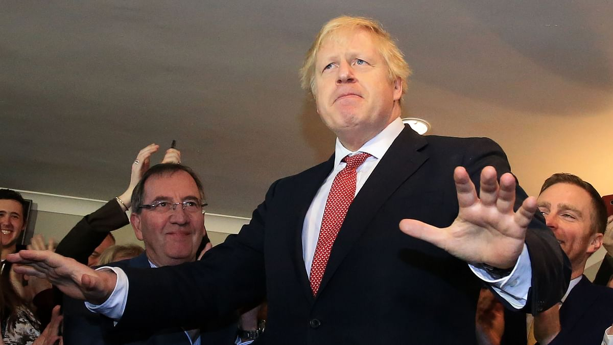 Britain's Prime Minister Boris Johnson gestures as he speaks to supporters on a visit to meet newly elected Conservative party MP for Sedgefield, Paul Howell at Sedgefield Cricket Club in County Durham, north east England on December 14, 2019, following his Conservative party's general election victory.