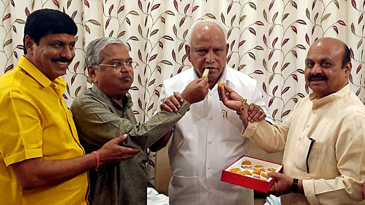 BJP leaders offer sweets to Karnataka Chief Minister BS Yediyurappa as his son BY Vijayendra, who won 12 out of 15 seats during the counting of votes of Karnataka by-polls, in Bengaluru on Monday.