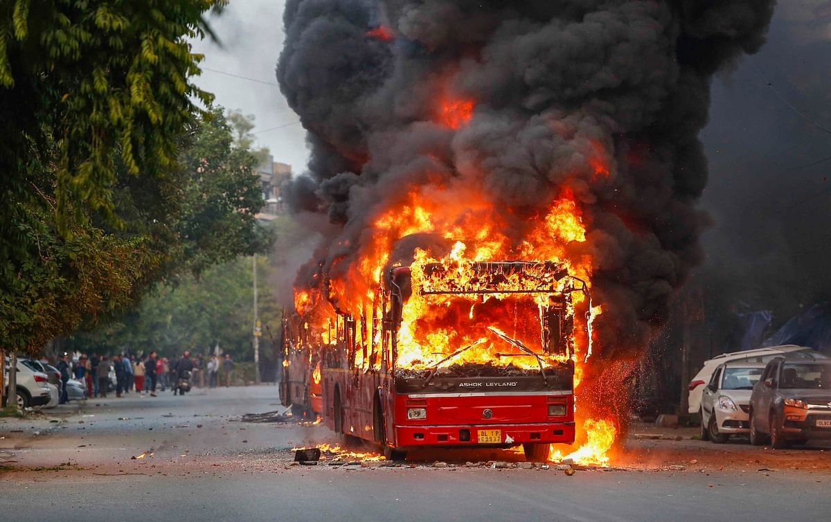 A public bus set on fire by anti-Citizenship Act protestors at Mathura Road, in New Delhi, Sunday, Dec. 15, 2019.