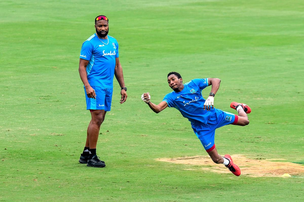 West Indies' captain Kieron Pollard (L) looks on as teammate Khary Pierre catches a ball during a training session ahead of the first T20 international cricket match of a three-match series between India and West Indies, at the Rajiv Gandhi International Cricket Stadium in Hyderabad on December 3, 2019.