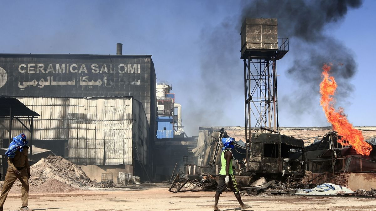 Men walk at the scene of a fire at a tile manufacturing unit in an industrial zone in Sudan's north Khartoum, on December 3, 2019.